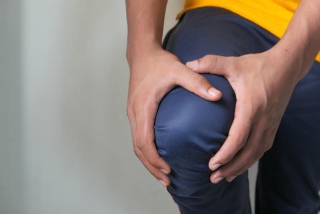 Primo piano sull'uomo che soffre di dolore alle articolazioni del ginocchio.