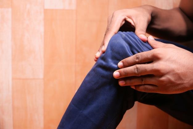 Primo piano sull'uomo che soffre di dolore alle articolazioni del ginocchio