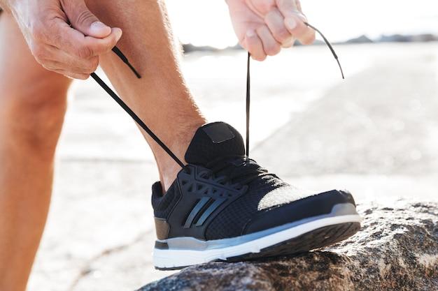 Chiuda in su di un uomo che lega i lacci delle scarpe