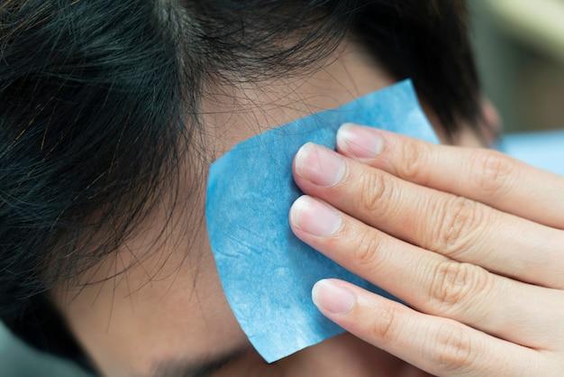 Primo piano su un uomo che usa carta assorbente per rimuovere l'olio dalla sua faccia