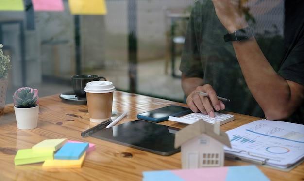 Primo piano uomo che utilizza calcolatrice e laptop per fare finanza matematica sulla scrivania di legno in ufficio e lavoro aziendale, tasse, contabilità, statistiche e concetto di ricerca analitica