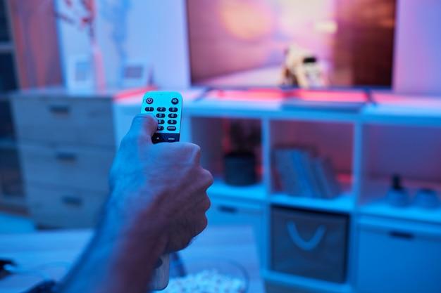 Primo piano dell'uomo usando il telecomando e cambiando i canali durante la visione della tv