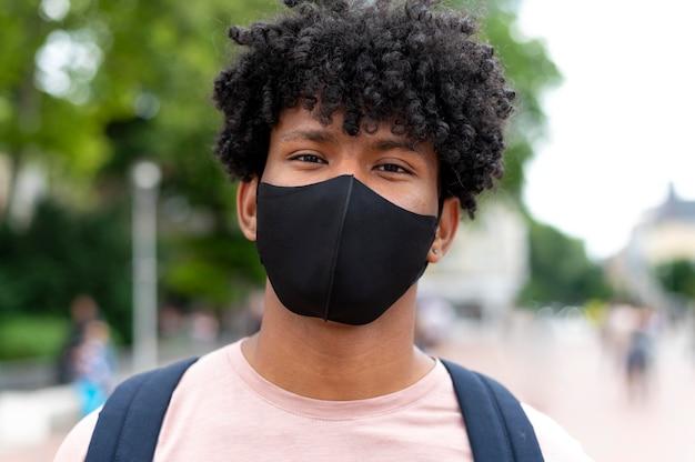 Primo piano uomo che indossa la maschera all'aperto