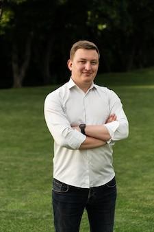 Primo piano di un uomo in camicia bianca che cammina nel parco in estate. uomo soddisfatto di aspetto europeo