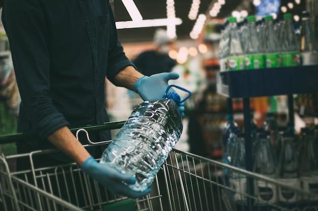 Avvicinamento. un uomo con una bottiglia di acqua potabile. igiene e assistenza sanitaria