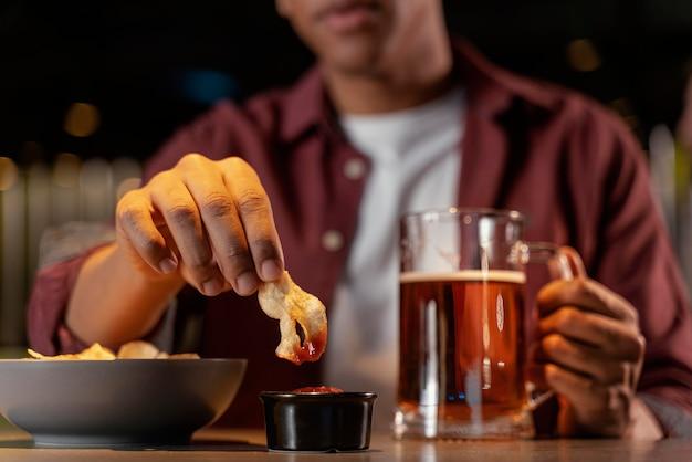 Uomo del primo piano con cibo e birra