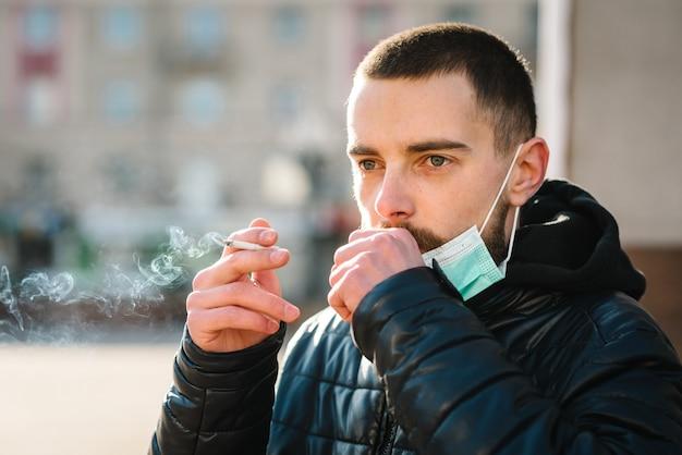 Chiuda sull'uomo con la maschera durante la pandemia covid-19 che tossisce e fuma una sigaretta alla via.