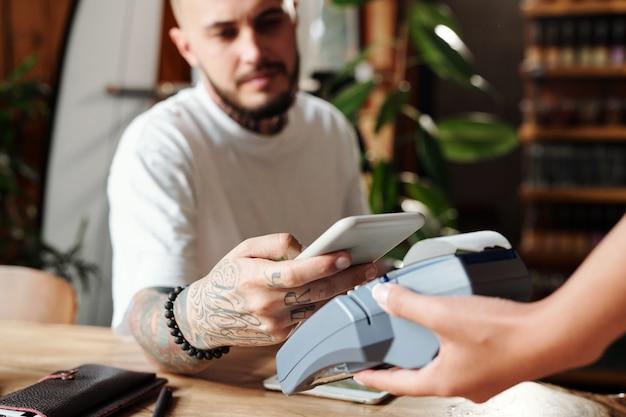 Primo piano dell'uomo con i tatuaggi che paga con lo smartphone dopo cena nella caffetteria moderna
