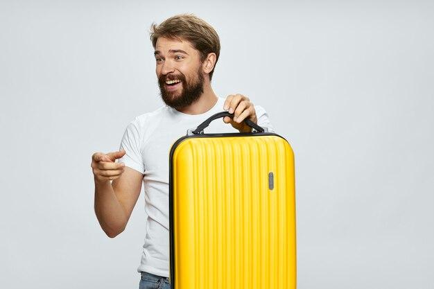 Primo piano sull'uomo con la valigia gialla isolata