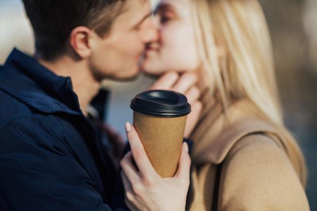 Primo piano di un uomo e di una donna sta baciando con mentre si cammina nel parco