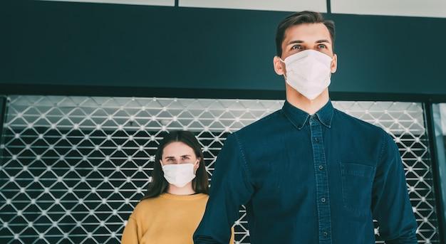 Avvicinamento. un uomo e una donna con maschere protettive in piedi uno accanto all'altro