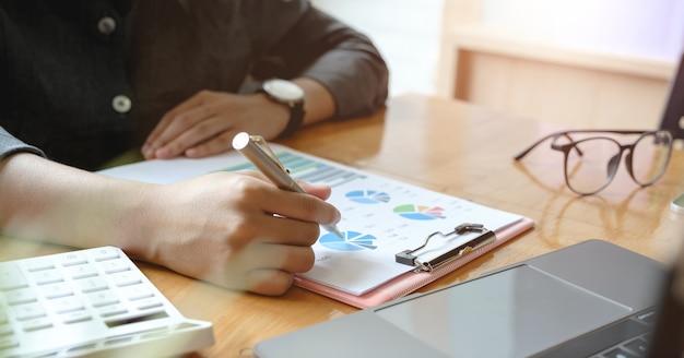 Chiuda su un uomo che lavora a finanziario con il calcolatore nel suo ufficio per calcolare le spese, concetto di contabilità