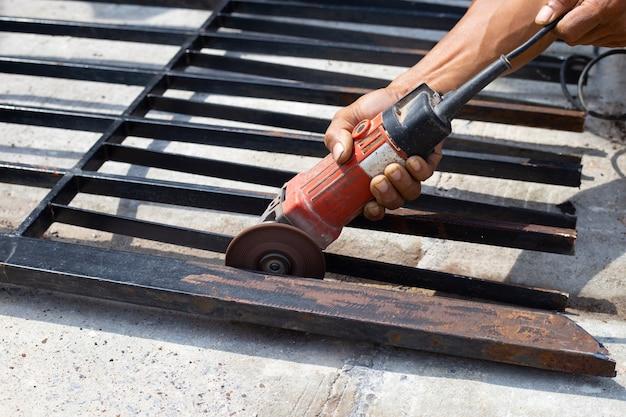 Primo piano, un uomo che lavora con una smerigliatrice angolare. riparazione cancello in ferro