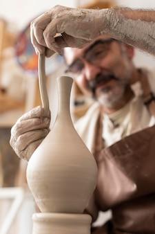 Primo piano uomo che lavora con l'argilla