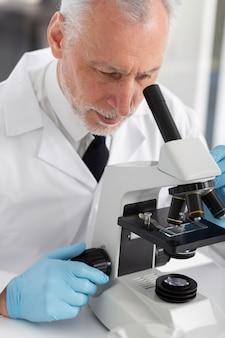 Close up uomo che lavora con il microscopio
