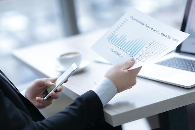 Primo piano del manager che lavora con i documenti finanziari