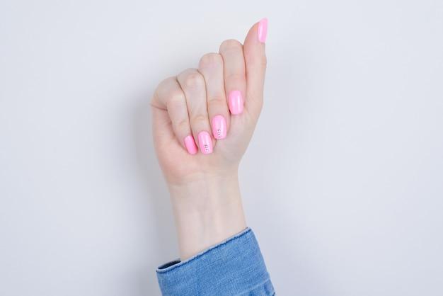Chiuda in su del manicure sulla mano della donna isolata
