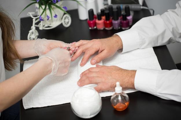 Primo piano di un manicurist tagliare la cuticola dalle dita della persona