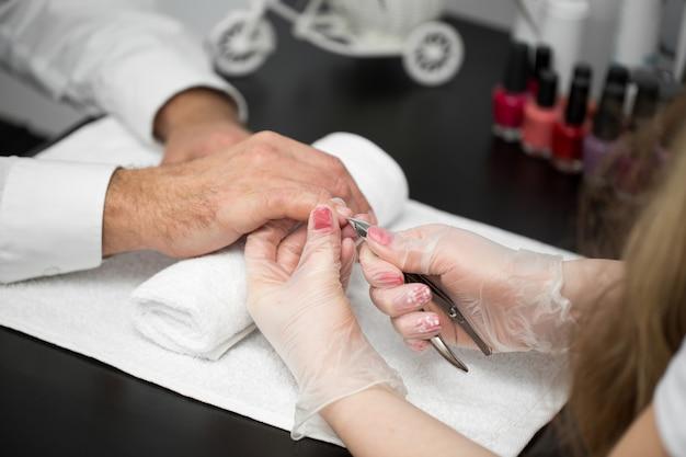 Primo piano di un manicure che taglia la cuticola dalle dita della persona Foto Premium