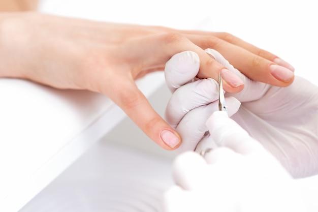 Chiuda in su del manicurist utilizzando le forbici per manicure per rimuovere la cuticola delle unghie femminili nel salone di manicure