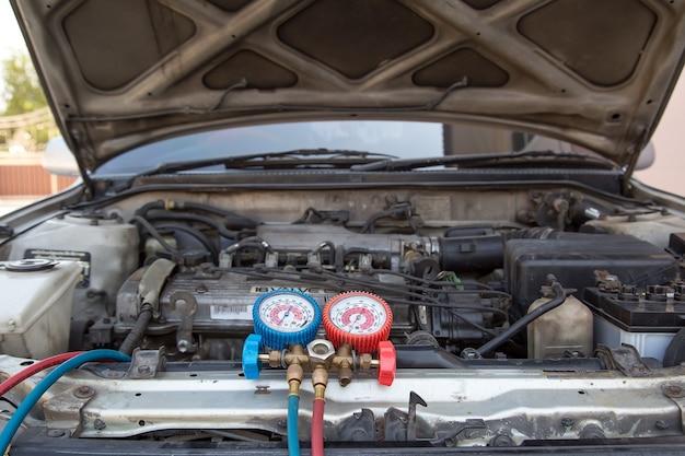 Primo piano il manometro del collettore misura lo strumento dell'attrezzatura per il riempimento dei condizionatori d'aria delle auto