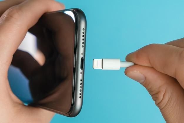 Primo piano mans mano inserendo un caricabatterie nel jack del telefono cellulare tramite un fulmine usb un cavo sulla superficie blu.