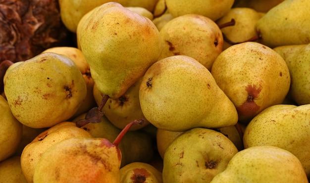 Chiudere molte pere gialle succose mature fresche sull'esposizione al dettaglio del mercato degli agricoltori, vista ad alto angolo