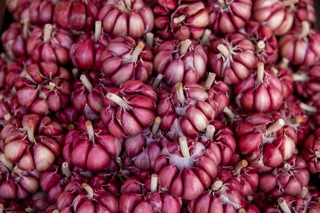 Primo piano di molte teste di aglio rosso sul supporto del mercato