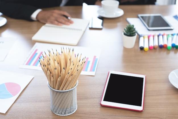 Close-up di molte matite sono nel cestino di metallo e posizionate sulla scrivania da lavoro, accanto c'è una cancelleria e il tablet desk office sul posto di lavoro. spazio per il testo
