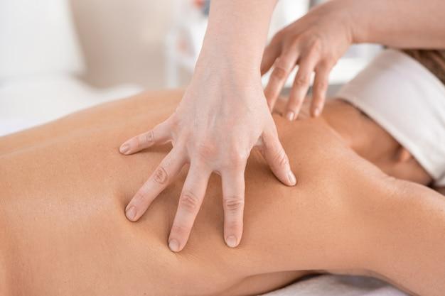 Primo piano del massaggiatore coccolare i muscoli della schiena della donna durante l'esecuzione del massaggio manuale nel salone della stazione termale