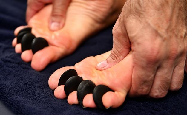 Primo piano di un massaggiatore che esegue una digitopressione ayurvedica sui piedi utilizzando pietre vulcaniche calde. concetti di cure termali