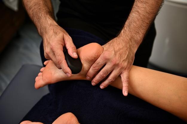 Primo piano del massaggiatore che esegue il massaggio ayurvedico utilizzando pietre calde vulcaniche. concetti di trattamento termale. concetto di cura del corpo