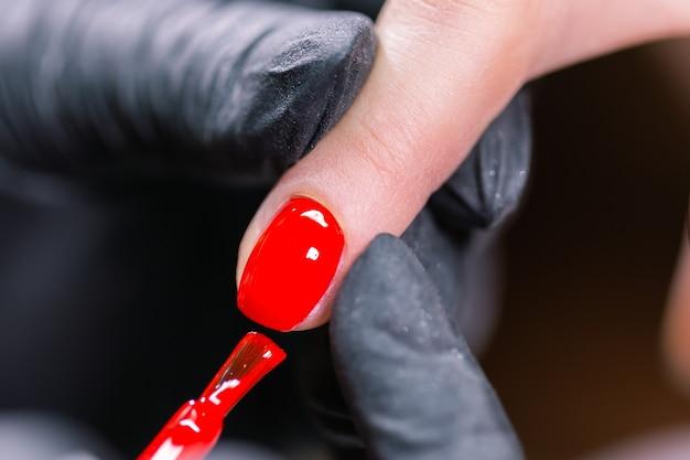 Primo piano del maestro in guanti di gomma che copre le unghie rosse con top coat nel salone di bellezza. perfetto