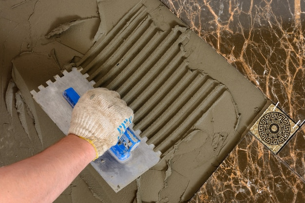 Primo piano della mano di un maestro che fa solchi in una soluzione glutinosa per la posa di piastrelle di marmo