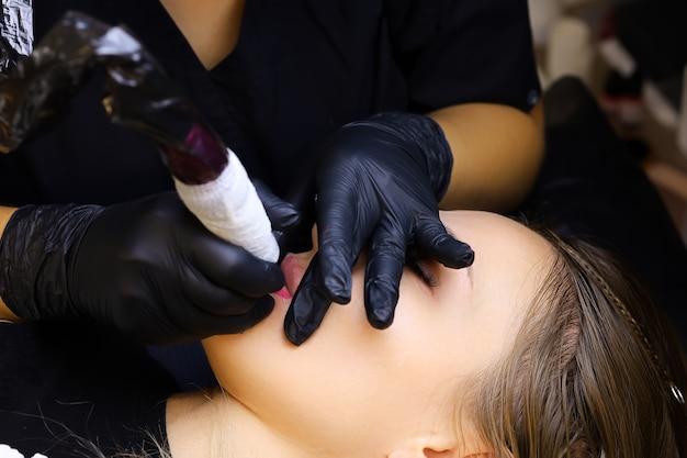 Primo piano del maestro che lavora con un tatuaggio delle labbra sul labbro inferiore della modella