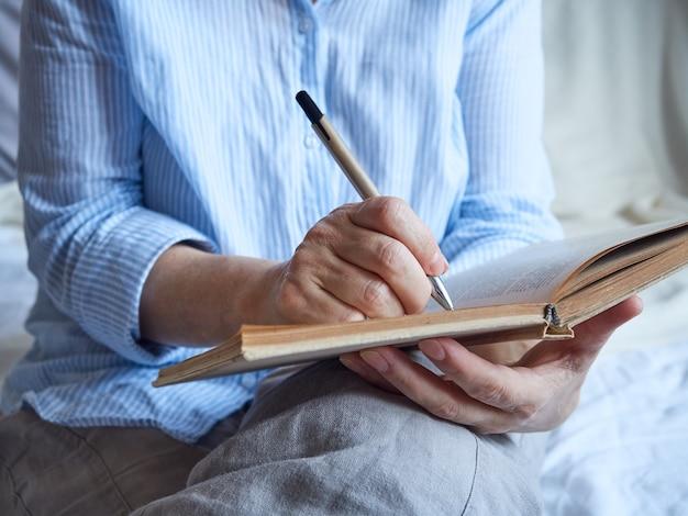 Primo piano del libro di lettura della mano della donna matura che fa i segni della matita.