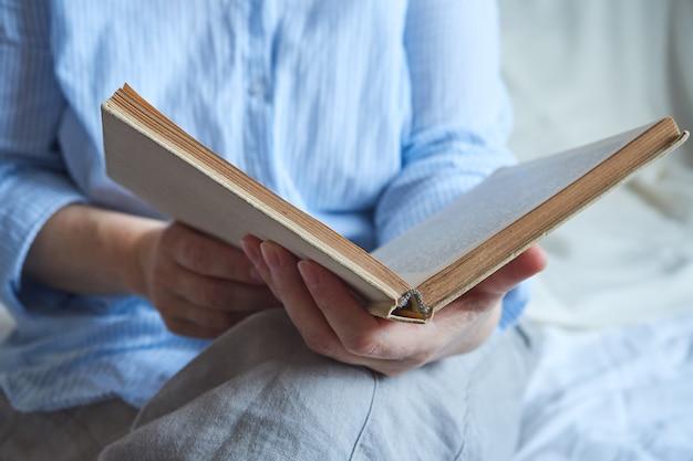Primo piano della mano di una donna matura che legge un libro.