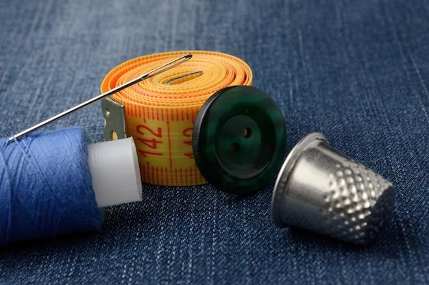 Primo piano del nastro di misurazione del rocchetto di filo e dei bottoni del ditale