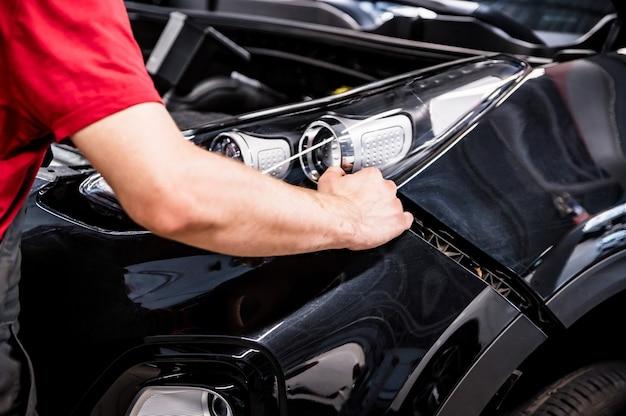 Primo piano delle mani del meccanico che smantellano il paraurti dell'auto