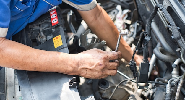Chiuda in su della chiave della holding della mano del meccanico davanti al motore di automobile con il cappuccio aperto.