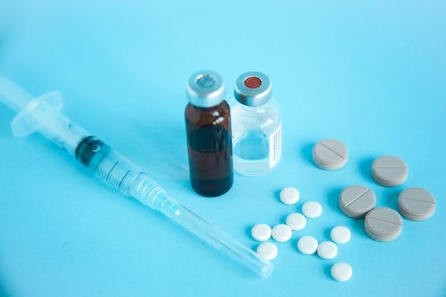 Chiuda in su della fiala medica, della siringa e delle pillole isolate sull'azzurro