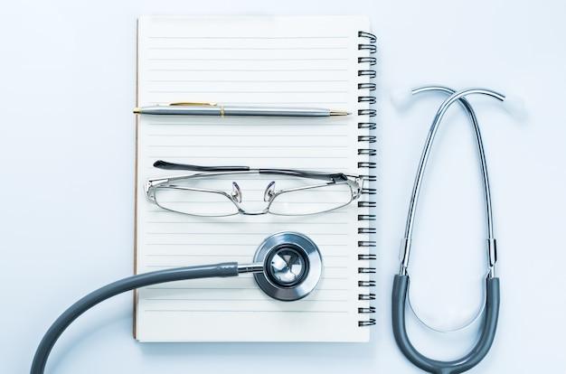 Primo piano stetoscopio medico con blocco note vuoto come concetto medico