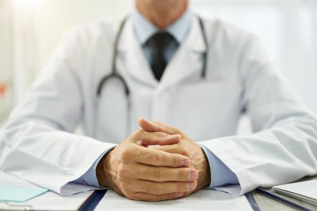 Primo piano dell'operatore medico in camice bianco seduto al tavolo e mettendo le mani sui fogli