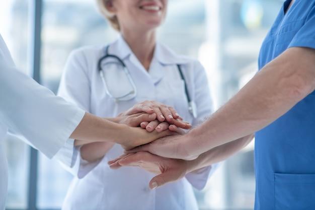 Primo piano degli operatori sanitari con le mani ammucchiate
