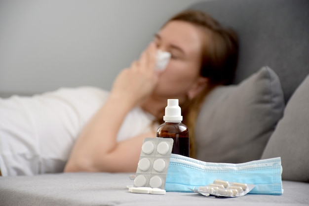 Chiuda in su su medicina, sciroppo, pillole e maschera protettiva e giovane donna che starnutisce e che copre la bocca di tovagliolo mentre tossisce. freddo, influenza, infezione, virus