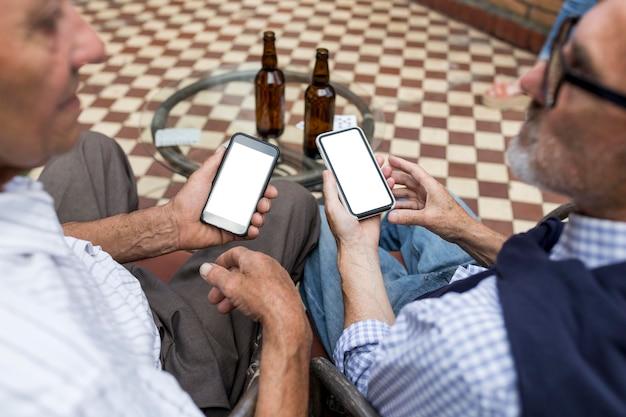 Uomini del primo piano che tengono gli smartphone