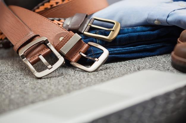 Chiuda sulla cinghia di cuoio degli uomini con vestiti su tappeto frabric