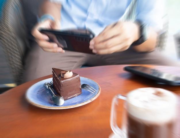 Primo piano delle mani degli uomini che fotografano il dessert dolce sul telefono cellulare per l'immagine dei social network mentre sono seduti al bar