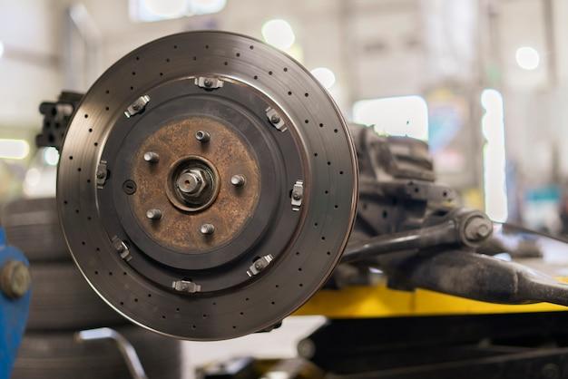 Un primo piano del disco del freno in metallo cromato, riparare le parti del veicolo dell'auto sportiva