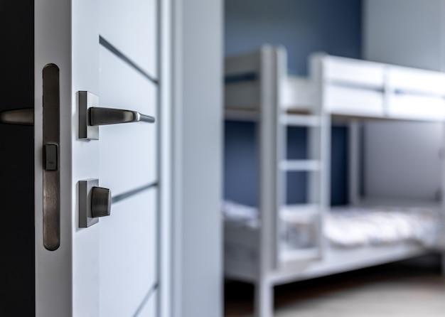 Primo piano della maniglia della porta in metallo su sfondo sfocato dell'interno della casa.